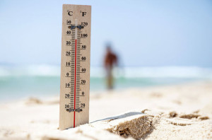 A thermometer shows hight temperature during a heatwave on the beach.